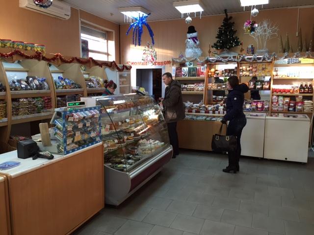 En julpyntad brödbutik hörde till brödfabriken och caféet Varmt Bröd. Kvinna bakom disken.